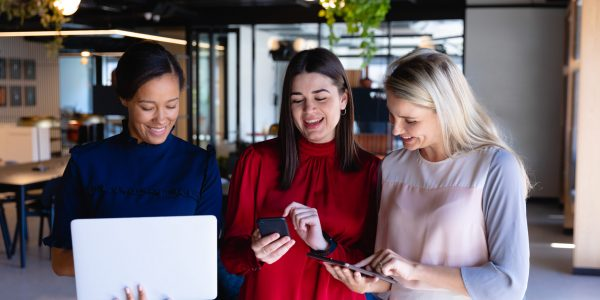 Front view of a group of three multi-ethnic businesswomen wearing smart clothes, working in a modern office, smiling and interacting, using a laptop, a smartphone and a tablet.